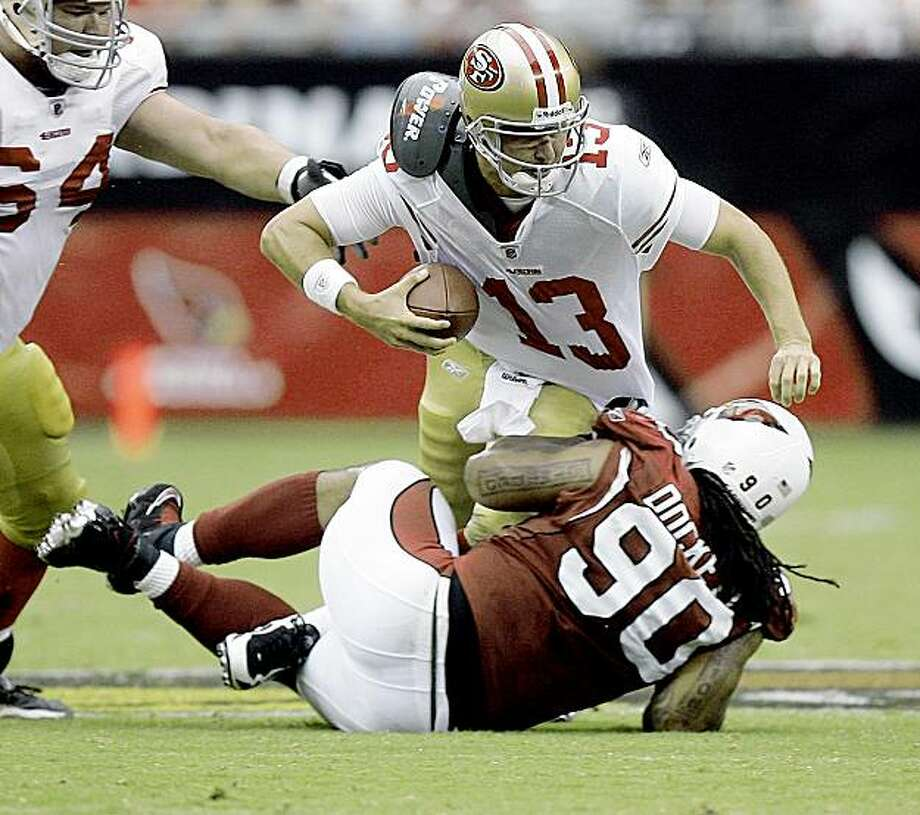 San Francisco 49ers quarterback Shaun Hill (13) is sacked by Arizona Cardinals defensive tackle Darnell Dockett (90) during the first half of an NFL football game Sunday, Sept. 13, 2009 in Glendale, Ariz. (AP Photo/Paul Connors) Photo: Paul Connors, AP