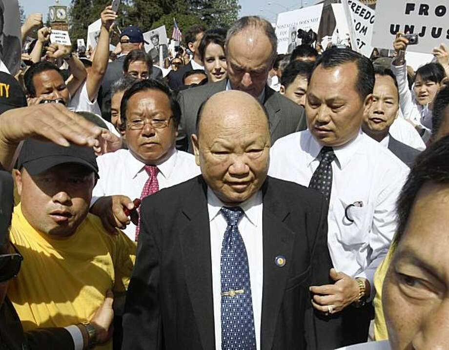 In this May 11, 2009 file photo former Laotian General Vang Pao, center, is escorted by supporters from the federal courthouse in Sacramento, Calif. A federal grand jury has dropped charges against Pao, Friday, of allegedly plotting to overthrow the government of Laos. Photo: Rich Pedroncelli, Associated Press