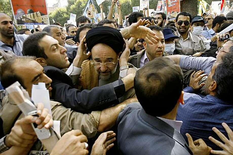 Escorted by his bodyguards, reformist former Iranian President Mohammad Khatami, center, is attacked by hard-liners as he attends a Quds Day rally, in Tehran, Iran, Friday, Sept. 18, 2009. At one of the opposition rallies, a group of hard-liners came up and attacked reformist former president, Mohammad Khatami, pushing him to the ground, according to a reformist Web site. Thousands of opposition supporters held protests in competition with government-sponsored mass rallies to mark an annual anti-Israel commemoration, the Quds Day that reflects the Persian nation's sympathy with the Palestinians. (AP Photo) Photo: STR, AP
