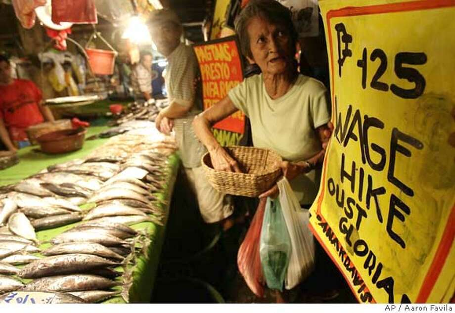 ###Live Caption:An activist buys fish at a public market with a budget of 85 pesos (about US$ 2) in suburban Quezon city, north of Manila, Philippines on Sunday, April 27, 2008. The demonstration was held to illustrate the alleged shortage in wages of workers due to the sharp increase in prices of food. (AP Photo/Aaron Favila)###Caption History:An activist buys fish at a public market with a budget of 85 pesos (about US$ 2) in suburban Quezon city, north of Manila, Philippines on Sunday, April 27, 2008. The demonstration was held to illustrate the alleged shortage in wages of workers due to the sharp increase in prices of food. (AP Photo/Aaron Favila)###Notes:###Special Instructions: Photo: AARON FAVILA
