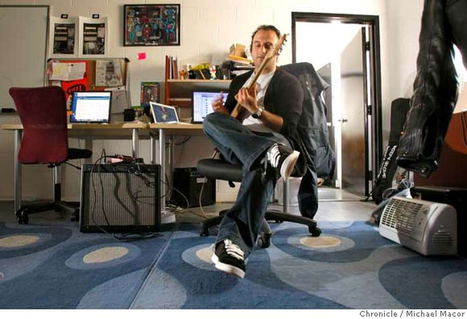 Arin Sarkissan, the director of Web Development for the online music site Fuzz, at company headquarters in San Francisco, Calif. on April 16, 2008. Fuzz helps bands to kep track of who is visiting their site as well as download music. Sarkissan takes a break from his computer to play of fgew licks on his guitar which is always close by his workstation.  Photo by Michael Macor/ San Francisco Chronicle Ran on: 04-21-2008  Arin Sarkissan, director of Web development for online music site Fuzz, plays a few licks on his guitar at his San Francisco office. Photo: Michael Macor