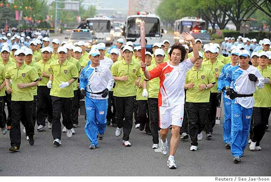 South Korean actor Song Il-gook runs with plainclothes policemen during the Beijing Olympic torch relay in central Seoul April 27, 2008. REUTERS/Seo Jae-hoon/Pool (SOUTH KOREA) KOREA OUT Photo: POOL