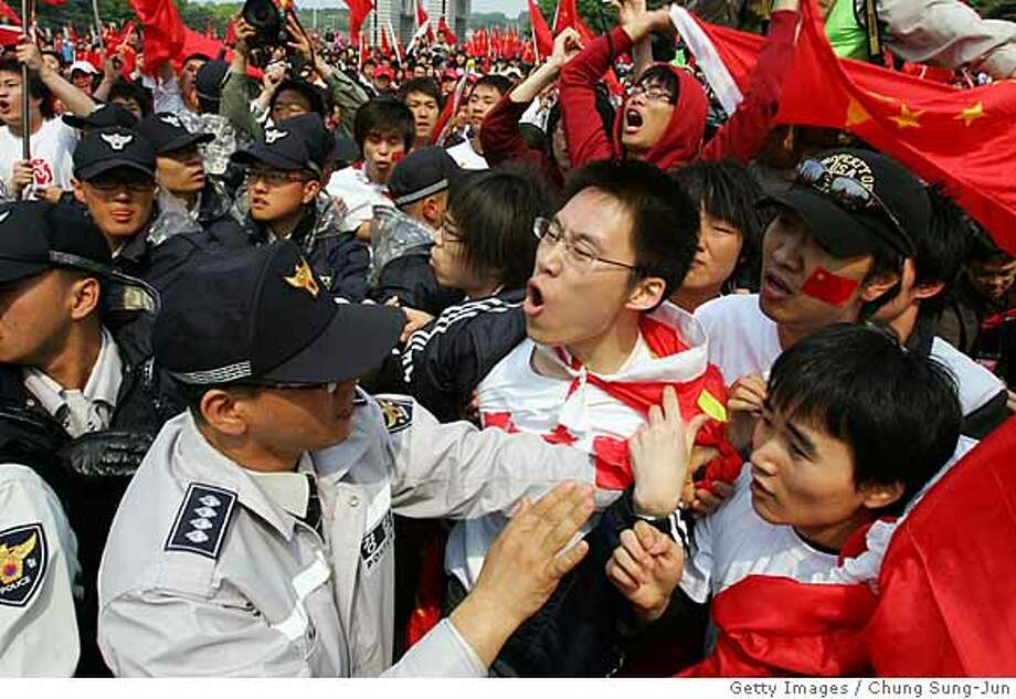 SEOUL, SOUTH KOREA - APRIL 27: South Korean policemen try to separate Chinese students and South Korean human rights for North Korea and Tibet activists after the start of the Olympic torch relay at Seoul Olympic park on April 27, 2008 in Seoul, South Korea. The Olympic flame travels through 19 countries and 43 cities, in addition to four communities, with 29 celebration events along the route. (Photo by Chung Sung-Jun/Getty Images) Photo: Chung Sung-Jun