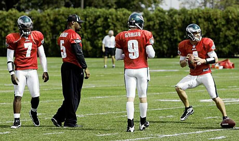 Philadelphia Eagles quarterbacks, from left, Michael Vick, Donovan McNabb, Jeff Garcia watch as Kevin Kolb drops back to pass during practice at the team's NFL football training facility, Wednesday, Sept. 23, 2009, in Philadelphia. (AP Photo/Matt Slocum) Photo: Matt Slocum, AP