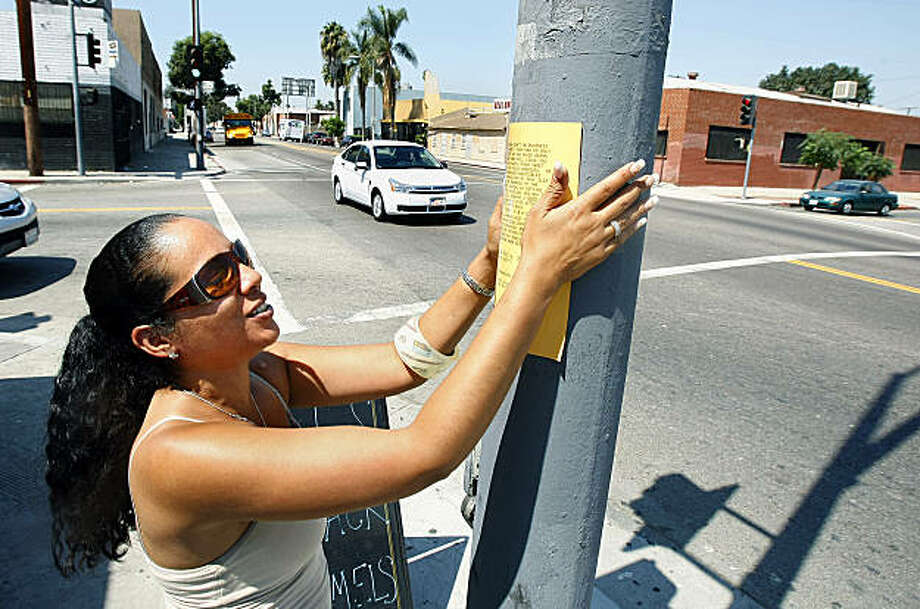 Adrienne Ferguson, co-founder of Alibis & Paybacks, posts a revenge flier outside an auto body shop in Los Angeles.  Adrienne Ferguson, co-founder of Alibis & Paybacks, posts a revenge flier outside an auto body shop in Los Angeles. Illustrates REVENGE (category a) by Bob Pool (c) 2009, Los Angeles Times. Moved Friday, Sept. 18, 2009. (MUST CREDIT: Los Angeles Times photo by Wally Skalij.) Photo: Wally Skalij, Los Angeles Times