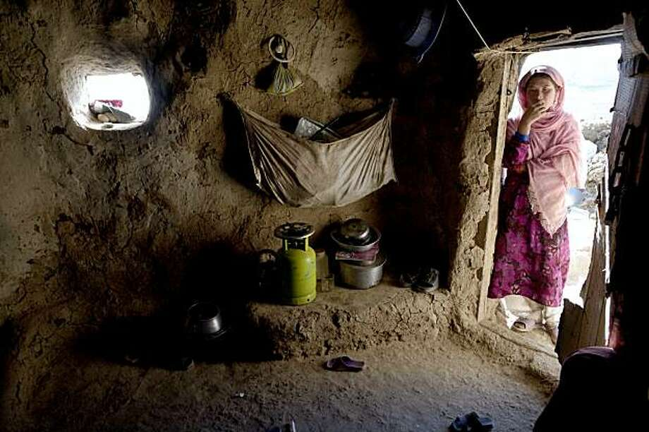 BAMIYAN, AFGHANISTAN -SEPTEMBER 2 :  Sukinah peers inside their cave dwelling September 2, 2009 in Bamiyan, Afghanistan. Many of the impoverished families living in the caves say they are too poor to live anywhere else even though the government insists that they are doing damage to an the area, near the giant Buddhas of Bamiyan, which is a rare archaeological site. All are refugees who fled areas of fighting during the Taliban era, and have now returned from the other parts of Afghanistan.  The cave dwellers are all Hazara, who are religiously and ethnically distinct and survivors of intense persecution by the Taliban. The Bamiyan region is the stronghold of the Hezb-i-Whadat party, the principal faction representing the Shia Muslims of the central area of Afghanistan.  (Photo Paula Bronstein/Getty Images) Photo: Paula Bronstein, Getty Images