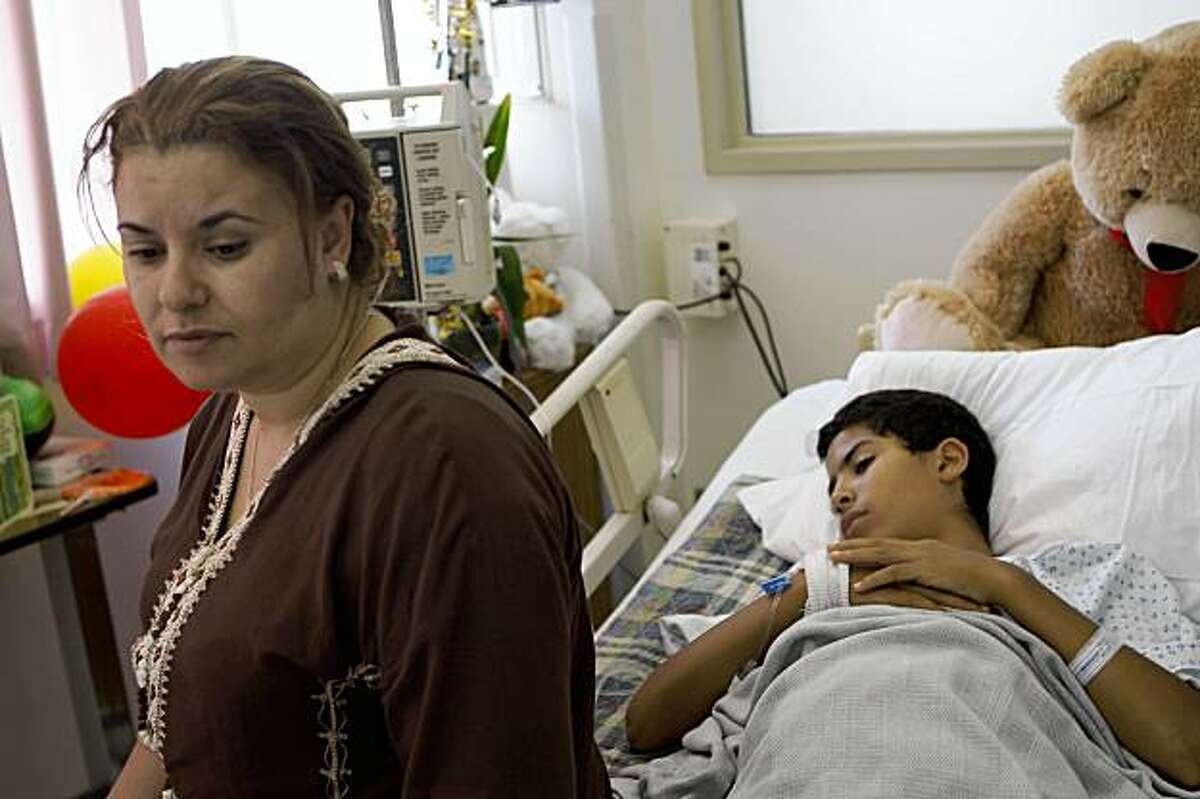 Laila Elfazouzi (left) sits with her son Hatim Mansori (right), 11 years old, at General Hospital in San Francisco, Calif. on Tuesday, September 8, 2009 where he is recovering after he was stabbed while riding home on the bus alone for the first time.