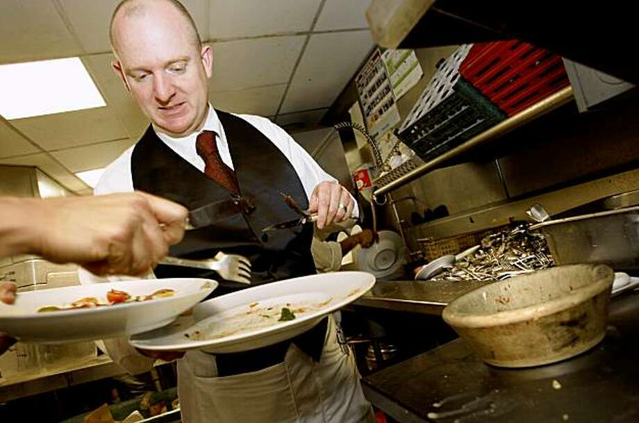 Boulevard waiter Iain Wallington helps remove food from the plates of diners which goes down a cylinder (right) into a green plastic composting container. San Francisco restaurants now have mandatory composting rules.  Boulevard Restaurant, on Mission Street near the Embarcadero, has been doing it for years. Photo: Brant Ward, The Chronicle