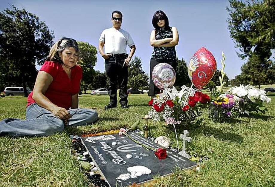 Parents Imelda, left, and Rafael Sierra and sister Fabiola Saavedra gather at the grave of Brenda Sierra on what would have been the young woman's 22nd birthday. Photo: Lawrence K. Ho , Los Angeles Times