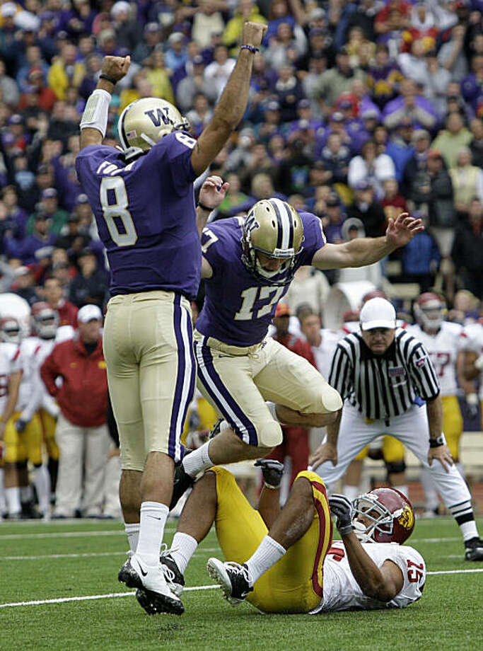 Washington's Erik Folk jumps out of the way of Southern California's Kevin Thomas as holder Ronnie Fouch celebrates Folk's game-winning field goal with seconds remaining in an NCAA college football game Saturday, Sept. 19, 2009, in Seattle. Washington upset USC 16-13. (AP Photo/Elaine Thompson) Photo: Elaine Thompson, AP