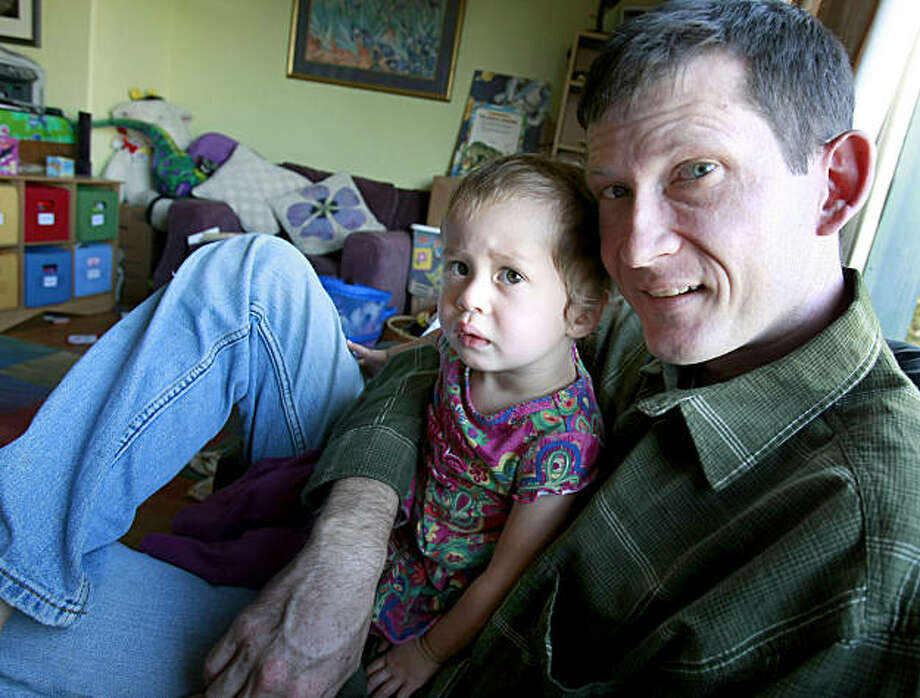 Yosha Bourgea sits with his youngest daughter, Josephine. Yosha Bourgea and his family are having a difficult time financially because of his underemployment.  A sharp cut in his paycheck as a teacher is forcing the family to move. Photo: Brant Ward, The Chronicle