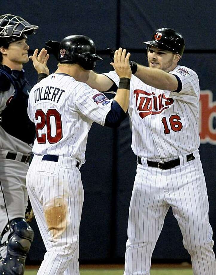 Minnesota Twins' Matt Tolbert, center, congratulates Jason Kubel, right, after Kubel's two-run home run off Cleveland Indians' Chris Perez in the eighth inning of a baseball game Monday, Sept. 14, 2009 in Minneapolis. At left is Indians catcher Lou Marson. The Twins won 6-3.  (AP Photo/Jim Mone) Photo: Jim Mone, AP