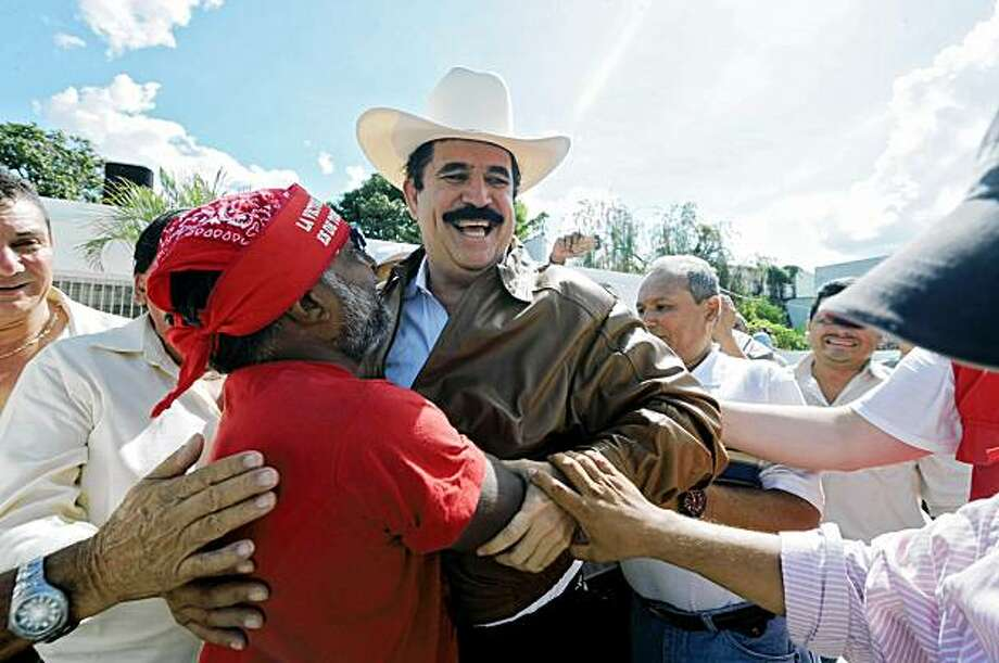 Ousted Honduran President, Manuel Zelaya (C), greets supporters at the Brazilian Embassy in Tegucigalpa on September 21, 2009. Zelaya made a surprise return to the country almost three months after soldiers expelled him in a coup.  AFP PHOTO / Orlando SIERRA (Photo credit should read ORLANDO SIERRA/AFP/Getty Images) Photo: Orlando Sierra, AFP/Getty Images