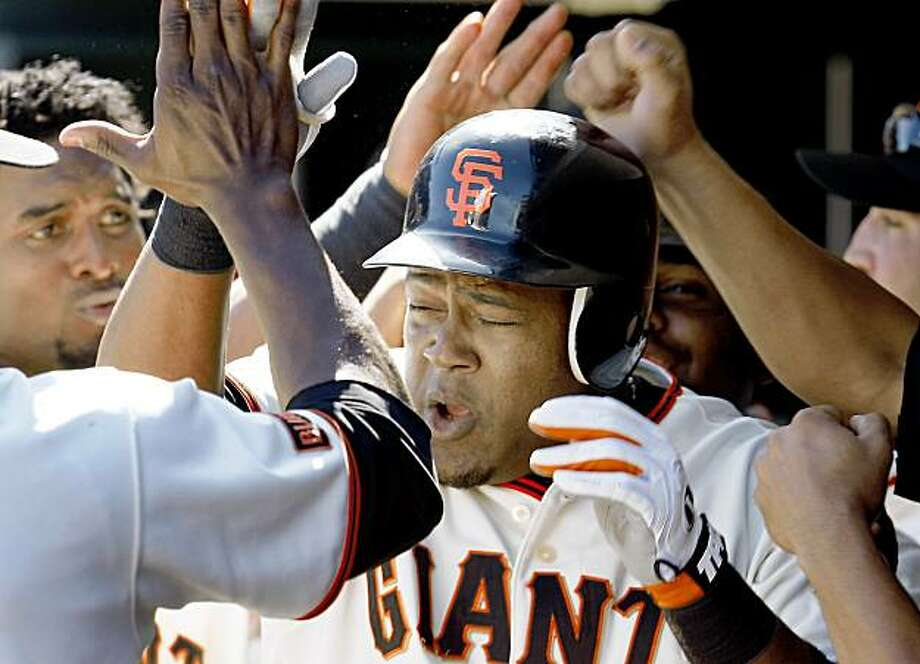Teammates pound the helmet of Juan Uribe after his 7th inning hthree run homer, his 6th run of the game. Giants vs. San Diego Padres at AT&T Park Monday September 7, 2009. Photo: Brant Ward, The Chronicle