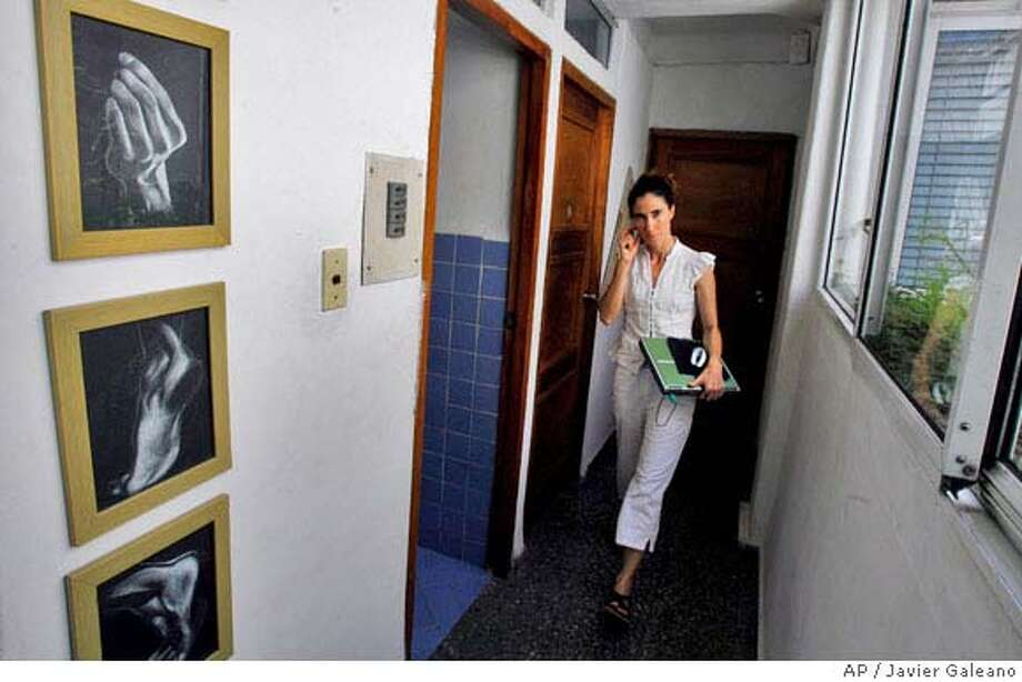 """** ADVANCE FOR MONDAY, APRIL 28 **Yoanis Sanchez, who writes the """"Generation Y"""" blog, walks inside her home in Havana, Friday, April 11, 2008. In Cuba, only foreigners and some government employees, researchers and academics are allowed Internet accounts, which are administered by the state.(AP Photo/Javier Galeano) Photo: Javier Galeano"""