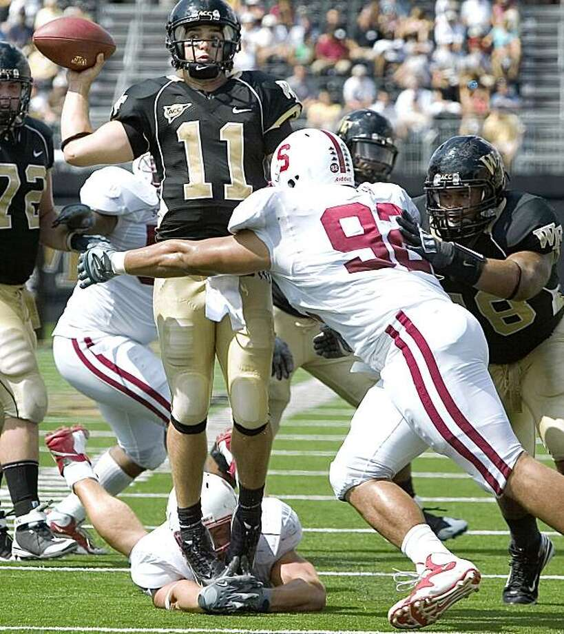 Wake Forest's quarterback Riley Skinner(11) throw under pressure from Stanford's Tom Keiser (92) and Tom Keiser (94) at his feet during the second half of an NCAA college football game in  Winston-Salem, N.C., Saturday, Sept. 12,  2009. Wake Forest wins 24-17. (AP Photo/Lynn Hey) Photo: Lynn Hey, AP