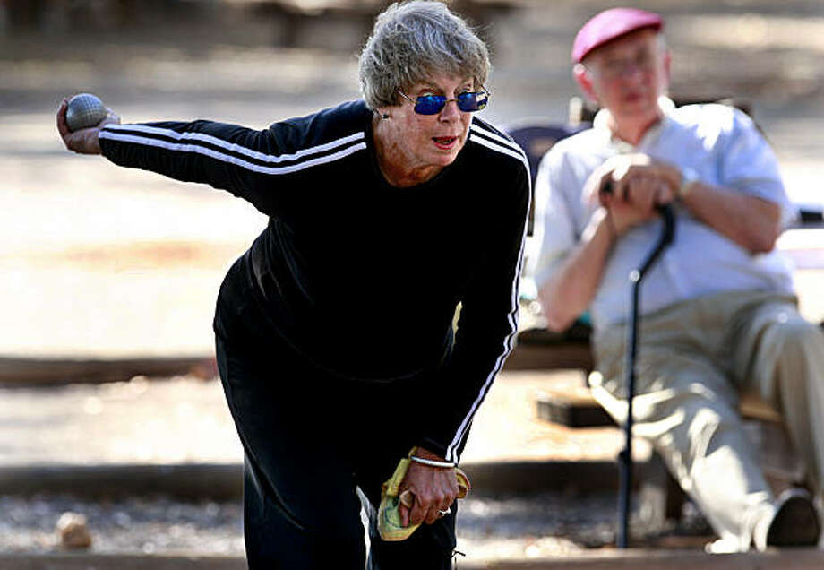 Cynthia gets ready for a shot while other players watch in the background. Cynthia Heinrichs plays Petanque, a French game that involves rolling balls around the dirt, but don't call it bocce. She and others gather at the Depot Park in Sonoma, CA Wednesday August 26, 2009. Photo: Brant Ward, The Chronicle