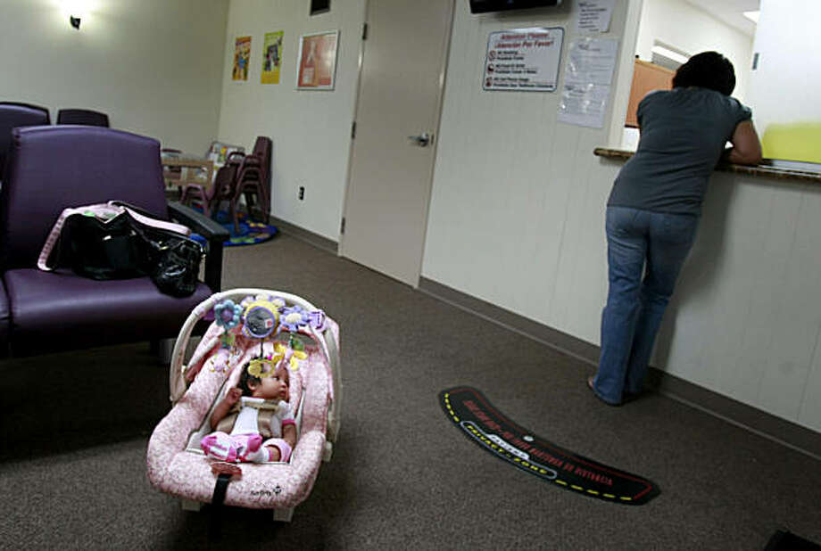 A new mother checks in at the clinic as her daughter waits. Photo: Brant Ward, The Chronicle