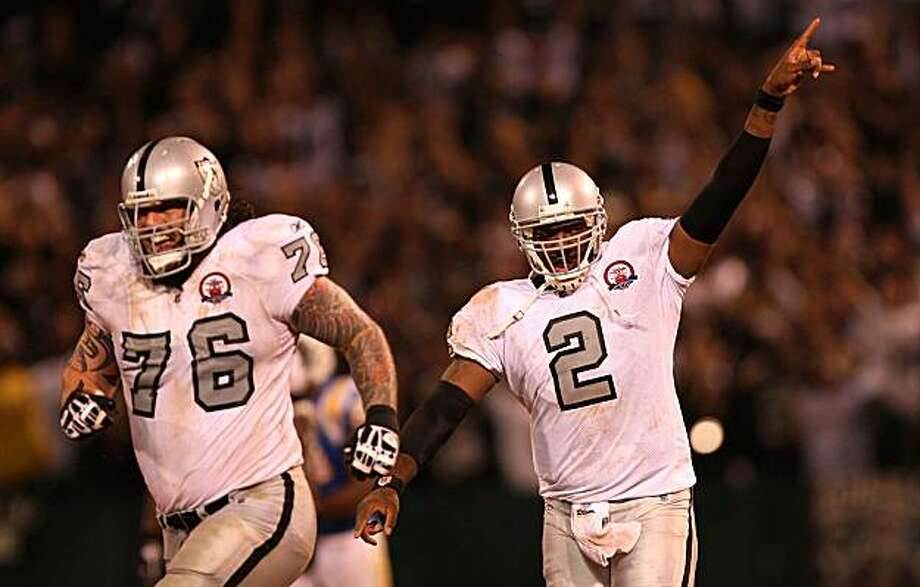 (Left to right) Robert Gallery (76) and JaMarcus Russell of the Oakland Raiders celebrate after Russell threw a 57-yard touchdown pass to Louis Murphy in the fourth quarter against the San Diego Chargers. Photo: Ezra Shaw, Getty Images