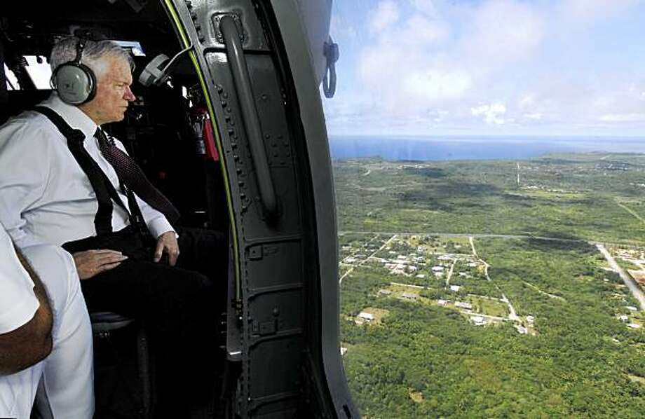 ** ADVANCE FOR SUNDAY SEPT. 6, AND THEREAFTER ** FILE - In this May 30, 2008 file photo provided by the US Department of Defense, U.S. Defense Secretary Robert M. Gates takes an aerial tour of the Island of Guam during a visit to Anderson Air Force Base, Guam. Gates toured military facilities, including areas planned for a substantial increase in construction to house more than 8,000 additional Marines expected to relocate from Japan's southern island of Okinawa in 2014. (AP Photo/US Department of Defense, Sgt. Jerry Morrison, FILE) ** ONLINE OUT ** Photo: Tech Sgt Jerry Morrison, AP