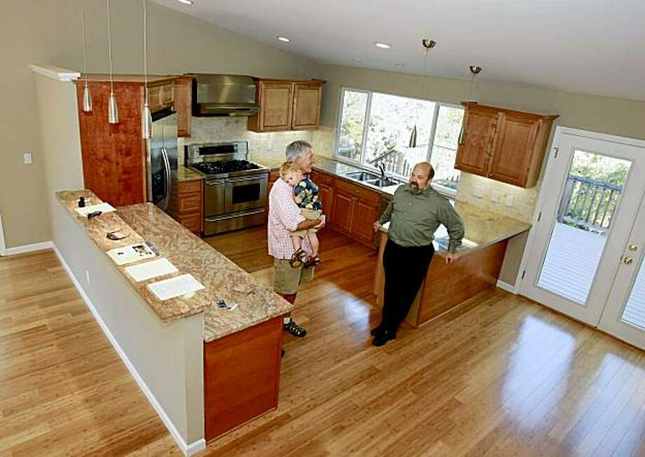 Kelley and his son (left) talk with real estate agent Peter Harris in the large kitchen area. John Kelley and his son Eamon, 2 years, walk through a $700,000 plus home in western Novato that they are considering purchasing. Photo: Brant Ward, The Chronicle