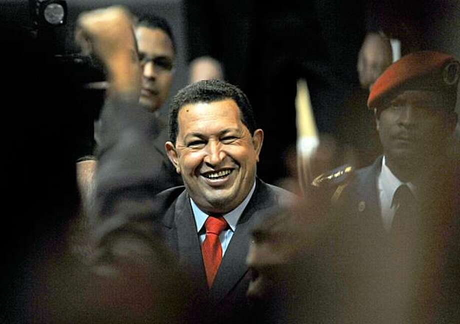 Venezuelan President Hugo Chavez greets supporters before the 2008 Liberator Prize for Critical Thinking award ceremony, granted to Hungarian-born British professor and philosopher Istvan Meszaros, in Caracas on September 14, 2009. The United States voiced alarm Monday that Venezuela's weapons purchases may be fueling a Latin American arms race after a deal between Caracas and Moscow to buy tanks and anti-aircraft rockets. In Caracas, Chavez said Sunday that Venezuela had obtained a 2.2-billion-dollar credit from Russia for the purchases, a move an analyst says suggests the leader's real fear of conflict over Venezuela's huge oil and gas resources.  AFP PHOTO/Juan BARRETO (Photo credit should read JUAN BARRETO/AFP/Getty Images) Photo: Juan Barreto, AFP/Getty Images