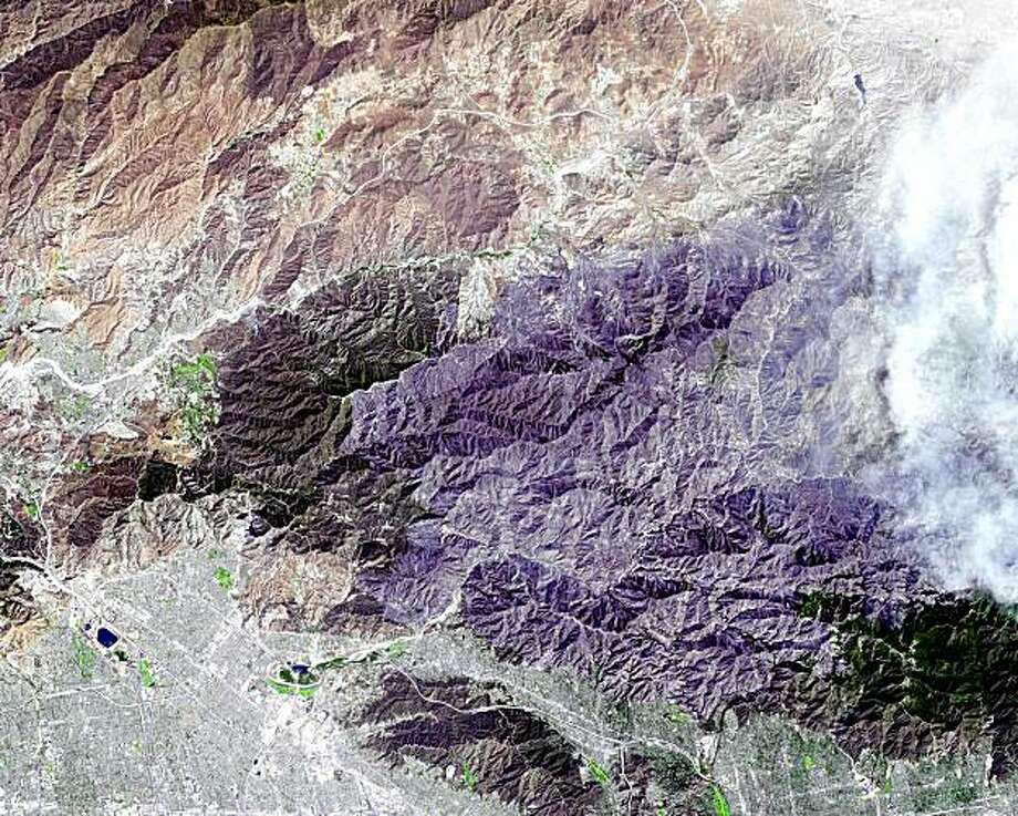 This image provided by NASA's Terra satellite on Tuesday Sept. 8, 2009, shows a satellite image of the Station Fire burning in Southern California. The fire started on August 26 in La Canada Flintridge near NASA's Jet Propulsion Laboratory in Pasadena, Calif.,and soon grew to become the largest fire in Los Angeles County's history, consuming more than 160,000 acres (251 square miles), leaving behind a charred, blackened landscape (center area) as it spread eastward. Smoke from the actively burning area can be seen on the right hand side of the image. (AP Photo/NASA) Photo: AP