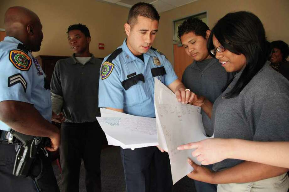 Officer Kendall Cobb talks to student Darius Cooper, 14,  as Officer Alvaro Vallejo shows Johnisha Granville, 14, and Jose Santos, 15, drawings of TAPS students goals for 2012 on Jan. 26 in Houston. Photo: Mayra Beltran / © 2012 Houston Chronicle