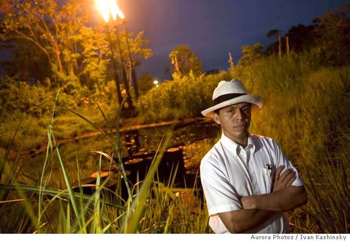 ###Live Caption:Pablo Fajardo stands in front of a pool of crude oil and waste and two towers that burn natural gas at the station North Lago Agrio in Lago Agrio, Ecuador, on December 17th, 2007. This pool of waste was left by Petro Ecuador, who took over after Texaco. Texaco passed on their bad practices to Petro Ecuador when they left the country. Pablo Fajardo is the lead attorney for the plaintiffs in the lawsuit against Texaco, which is now owned by Chevron. For twenty years Texaco was responsible for recklessly disposing of crude oil and toxic waste which leaked into the water supply of the people living in theses areas. There is now a higher rate of cancer, birth defects, and skin diseases. The 6 billion dollar case has been dragged out for 14 years. Pablo, who grew up in proverty and witnessed first hand the devastation brought to the people and environment because of the reckless behavior of Texaco, works on the case day and night. He just recently won the CNN Hero award in the category of fighting for justice, which has put the spotlight on the case that Chevron is is doing it's best to keep low profile. The six billion dollars that the people of the Ecuadorian jungle are asking of Texaco/Chevron would be used to clean up the the pools of crude oil which are still seeping into the environment. Photo by Ivan Kashinsky / Aurora Photos###Caption History:Pablo Fajardo stands in front of a pool of crude oil and waste and two towers that burn natural gas at the station North Lago Agrio in Lago Agrio, Ecuador, on December 17th, 2007. This pool of waste was left by Petro Ecuador, who took over after Texaco. Texaco passed on their bad practices to Petro Ecuador when they left the country. Pablo Fajardo is the lead attorney for the plaintiffs in the lawsuit against Texaco, which is now owned by Chevron. For twenty...