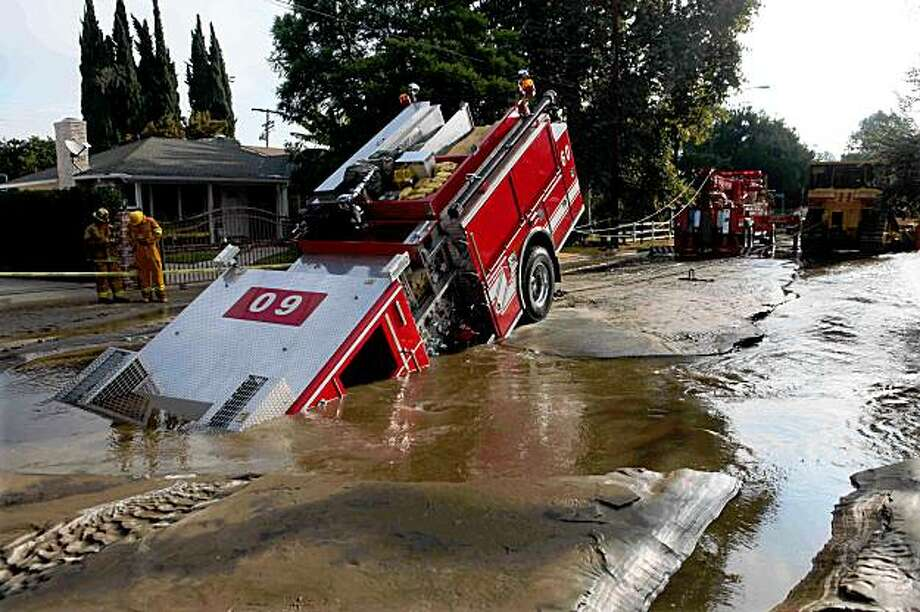 A Los Angeles fire truck is pulled from a sinkhole in the Valley Village neighborhood of Los Angeles Tuesday, Sept. 8, 2009. Four firefighters escaped injury early Tuesday after their fire engine sunk into a large hole caused by a broken water main in the San Fernando Valley, authorities said.  (AP Photo/Nick Ut) Photo: Nick Ut, AP