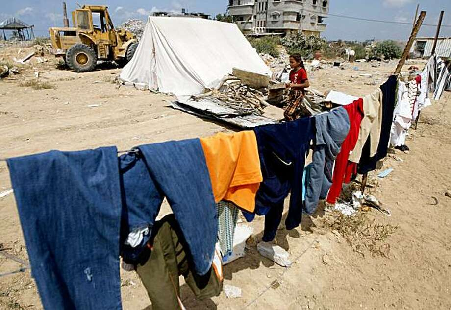 A Palestinian girl who is a member of the Samouni family walks past a tent next to the remains of their house which was destroyed during Israeli's January offensive, in Gaza City, Wednesday, Sept. 16, 2009. The Samouni family lost more than 20 members of their family during the last Israeli offensive in the Gaza Strip. Israel on Wednesday rejected U.N. calls to open an independent inquiry into its conduct in last winter's Gaza Strip war and said it would launch a diplomatic offensive to block any attempt to bring its soldiers before an international war crimes tribunal. Photo: Khalil Hamra, AP