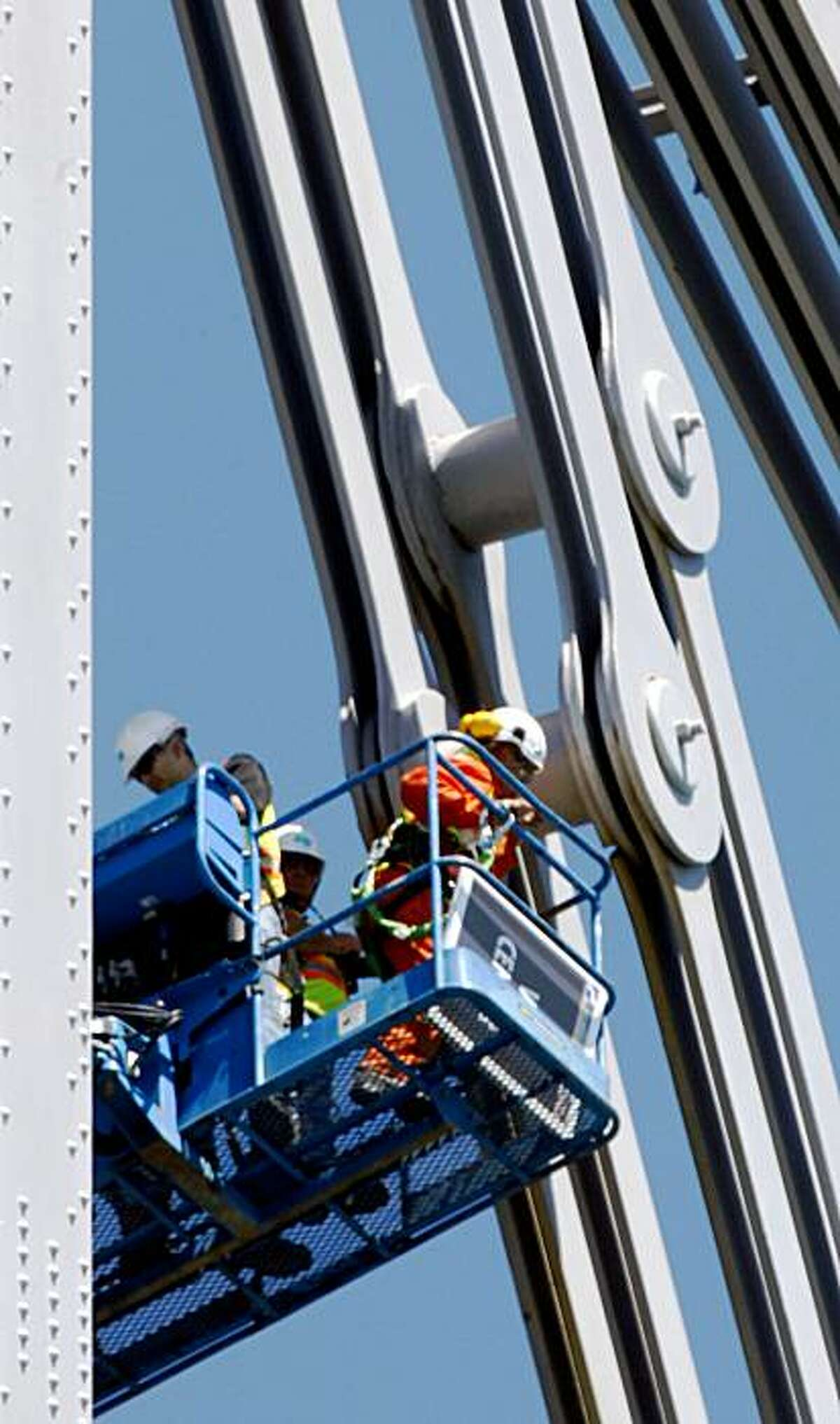 Caltrans workers survey the crack in the inside eyebar on the old boxed steel frame portion of the Bay Bridge on Sunday.