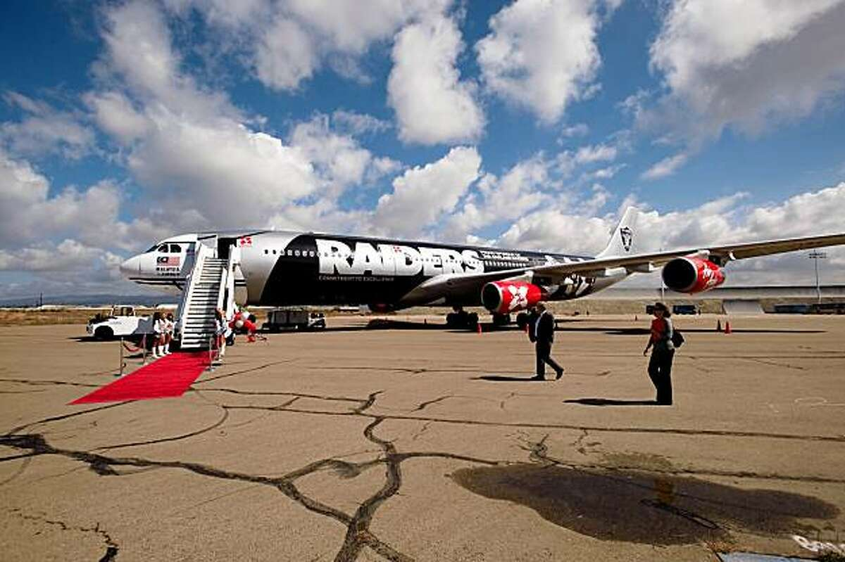 An Oakland Raider-emblazoned Air Asia A30 jet rolls out the red carpet at Oakland International Airport.