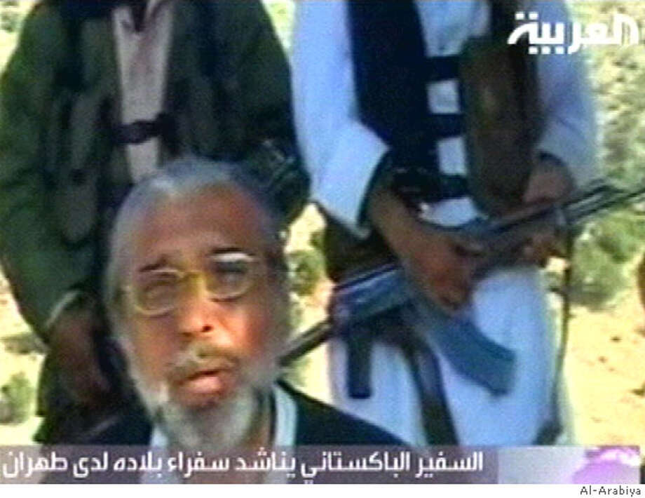In this photo, taken from Al-Arabiya satellite channel television video, Pakistan's ambassador to Afghanistan Tariq Azizuddin appears on a video aired Saturday, April 19, 2008, saying he was kidnapped by Taliban militants more than two months ago. Men wearing traditional robes and holding automatic weapons stand behind him.(AP Photo/Al-Arabiya ) Photo: Al-Arabiya