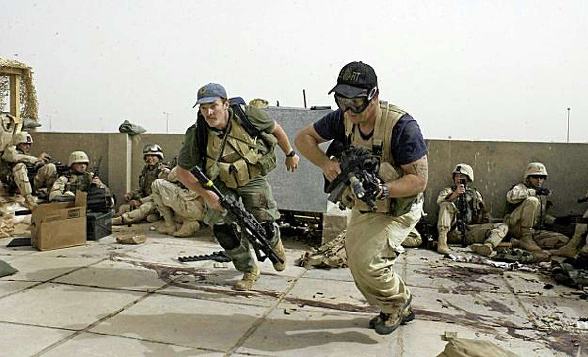 In this April 4, 2004 file photo, plainclothes contractors working for Blackwater USA take part in a firefight as Iraqi demonstrators loyal to Muqtada Al Sadr attempt to advance on a facility being defended by U.S. and Spanish soldiers in Najaf, Iraq. The security firm once known as Blackwater Worldwide will continue protecting American diplomats in Iraq for months to come, far longer than has previously been acknowledged, even though the company has no license to operate in the country and has been told by the State Department that its contracts will not be renewed.