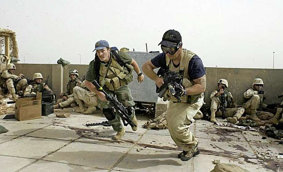 In this April 4, 2004 file photo, plainclothes contractors working for Blackwater USA take part in a firefight as Iraqi demonstrators loyal to Muqtada Al Sadr attempt to advance on a facility being defended by U.S. and Spanish soldiers in Najaf, Iraq. The security firm once known as Blackwater Worldwide will continue protecting American diplomats in Iraq for months to come, far longer than has previously been acknowledged, even though the company has no license to operate in the country and has been told by the State Department that its contracts will not be renewed. Photo: Gervasio Sanchez, AP
