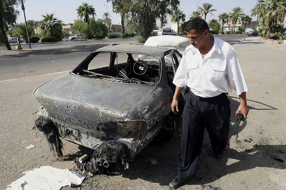 ** FILE ** In this Sept. 20, 2007 file photo, an Iraqi traffic policeman inspects a car destroyed by a Blackwater security detail in al-Nisoor Square in Baghdad, Iraq. (AP Photo/Khalid Mohammed, File) Photo: Khalid Mohammed, File, AP