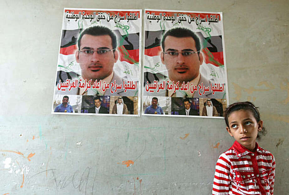 A young relative of jailed Iraqi journalist Muntazer al-Zaidi, stands under his poster as his family makes his apartment ready for his upcoming release, in central Baghdad on September 10, 2009. Zaidi became a star in the Arab world when he hurled his shoes at visiting US President George W. Bush on December 14, 2008, during a press conference in Baghdad. AFP PHOTO / AHMAD AL-RUBAYE (Photo credit should read AHMAD AL-RUBAYE/AFP/Getty Images) Photo: Ahmad Al-Rubaye, AFP/Getty Images