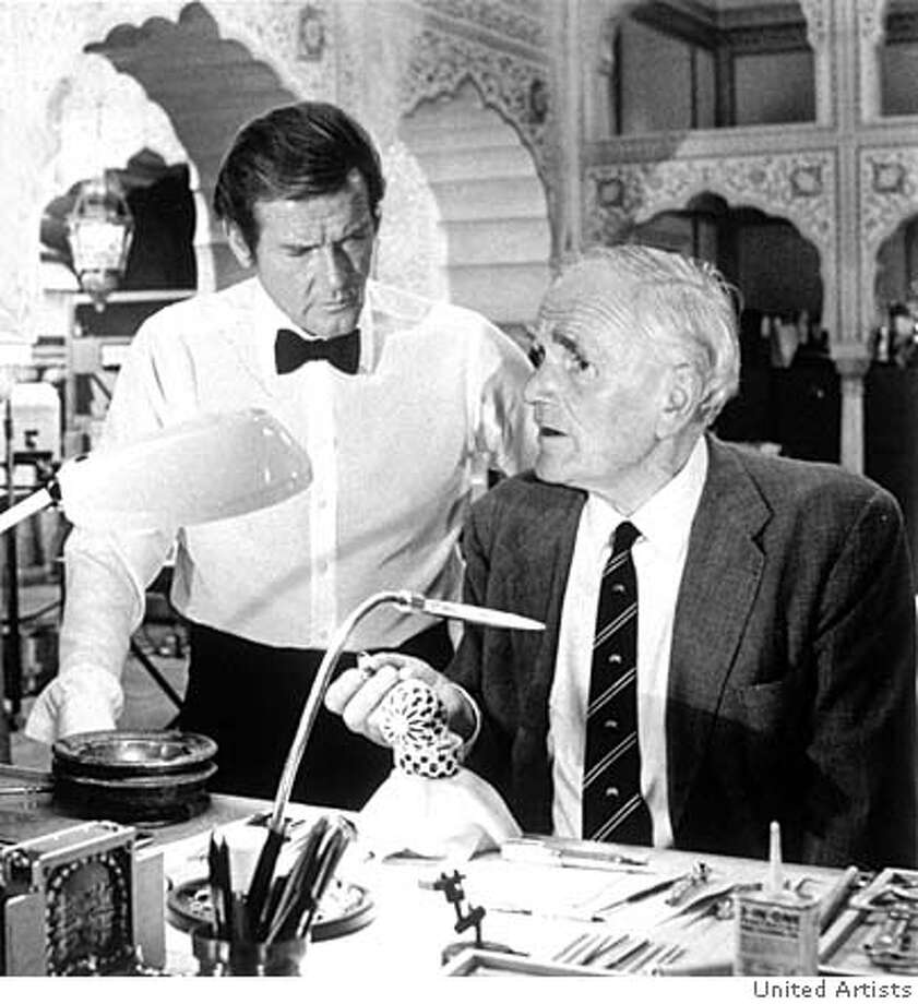 ###Live Caption:Roger Moore as James Bond stands with Desmond Llewelyn as Q in Octopussy.###Caption History:THIS IS A IMAGE. PLEASE VERIFY RIGHTS. BOND23a-C-20NOV02-DD-HO  Roger Moore as James Bond stands with Desmond Llewelyn as Q in Octopussy.  James Bond Films � 1962-2002 Danjaq, LLC and United Artists Corporation. All Rights Reserved. 007 Gun Symbol Logo � 1962 Danjaq, LLC and United Artists Corporation. All Rights Reserved. James Bond, 007 Gun Symbol Logo and all other Bond related trademarks TM Danjaq, LLC.  � 2002 MGM Home Entertainment Inc. All Rights Reserved.###Notes:###Special Instructions: Photo: HANDOUT
