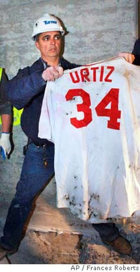 Frank Gramarossa, project executive for the new Yankee Stadium, displays a Boston Red Sox jersey with the name of player David Ortiz that was removed from the ground at the new Yankee Stadium in New York, Sunday, April 13, 2008. The Yankees have ended a construction worker's attempt to jinx their new stadium with the buried jersey. (AP Photo/Frances Roberts) Photo: FRANCES ROBERTS