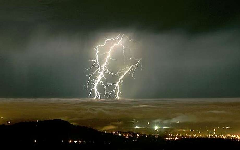 With a layer of coastal stratus coating the valley floor of Santa Rosa and Healdsburg, Calif. moisture from tropical storm Linda is seen as lightning stikes, early Saturday Sept. 12, 2009 over Sonoma County. (AP Photo/Press Democrat, Kent Porter) **MAGS OUT, NO SALES** Photo: Kent Porter, AP