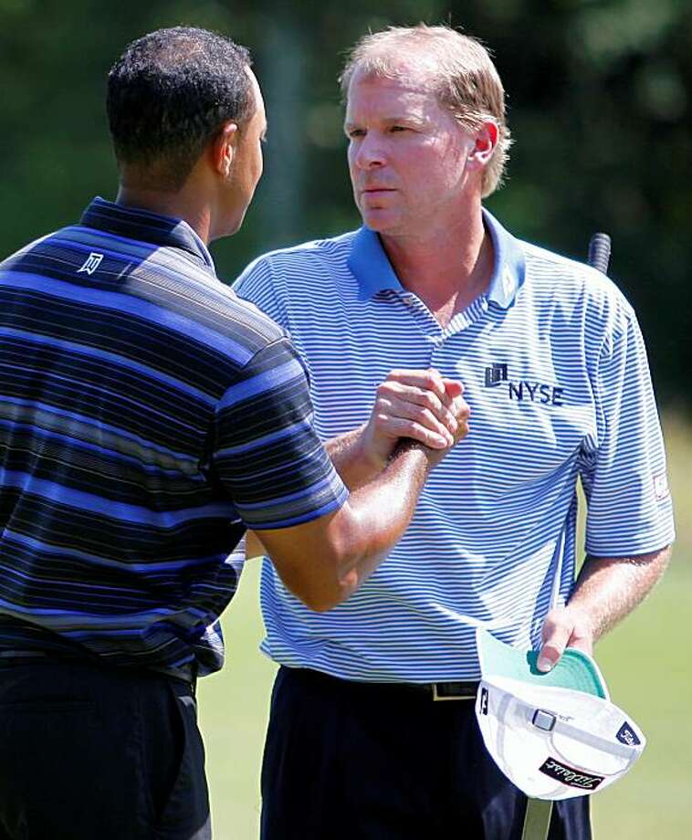 Tiger Woods, left, and Steve Stricker shake hands on the ninth hole after finishing the first round of the Deutsche Bank Championship golf tournament in Norton, Mass., Friday, Sept. 4, 2009. (AP Photo/Michael Dwyer) Photo: Michael Dwyer, AP