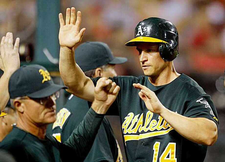 ANAHEIM, CA - AUGUST 29:  Mark Ellis #14 of the Oakland Athletics receives high fives from his teammates after scoring on a wild pitch in the seventh inning against the Los Angeles Angels of Anaheim at Angel Stadium on August 29, 2009 in Anaheim, California.  (Photo by Jeff Gross/Getty Images) Photo: Jeff Gross, Getty Images