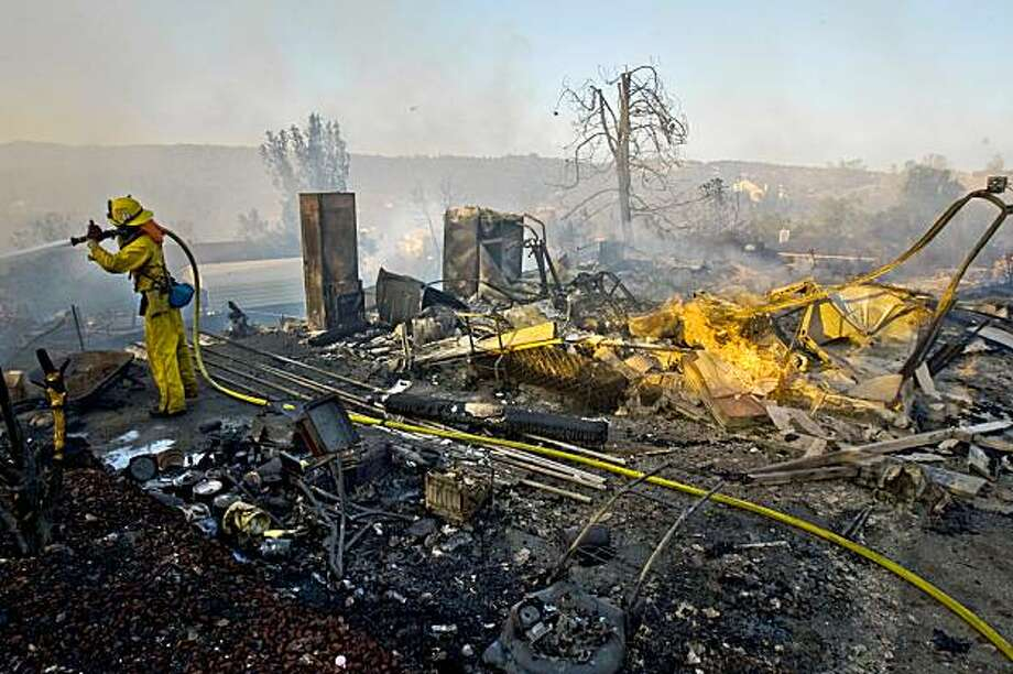 Firefighters pour water on hot spots of a house that burned along Cedar Mist Ln. in Auburn, California on Aug. 30, 2009, after a fast moving wildfire swept through a business district and residential neighborhood destroying dozens of home and business. Photo: Peter DaSilva, Special To The Chronicle