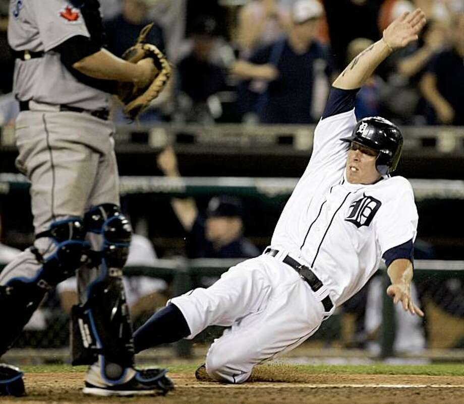 Detroit Tigers' Brandon Inge scores from second base to defeat the Toronto Blue Jays 6-5 in the 10th inning of a baseball game Monday, Sept. 14, 2009 in Detroit. Inge scored when Alex Avila's grounder, fielded by Blue Jays first baseman Lyle Overbay, went off the glove of shortstop Mrco Scutaro for an error.  (AP Photo/Duane Burleson) Photo: Duane Burleson, AP