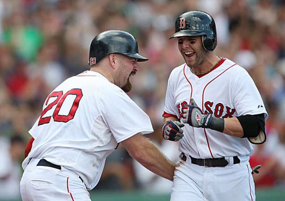 BOSTON - SEPTEMBER 13:  Dustin Pedroia #15 of the Boston Red Sox is congratulated by teammate Kevin Youkils #20 after Pedroia hit the game winning home run against the Tampa Bay Rays on September 13, 2009 at Fenway Park in Boston, Massachusetts. Pedroia drove in pinch runner Joey Gathright on the play. The Red Sox defeated the Rays 3-1. (Photo by Elsa/Getty Images) Photo: Elsa, Getty Images