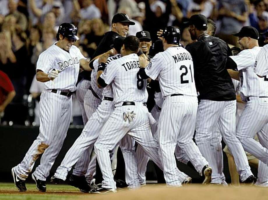 Members of the Colorado Rockies mob Seth Smith after his single drove in two runs against the Cincinnati Reds in the ninth inning of the Rockies' 4-3 victory in a baseball game in Denver on Wednesday, Sept. 9, 2009. (AP Photo/David Zalubowski) Photo: David Zalubowski, AP