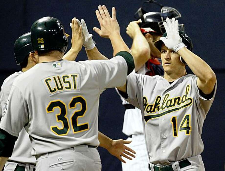 Oakland Athletics' Mark Ellis (14) is congratulated by teammates Jack Cust (32) and Kurt Suzuki after his three-RBI home run during the third inning of a baseball game against the Minnesota Twins in Minneapolis, Friday, Sept. 11, 2009. (AP Photo/Ann Heisenfelt) Photo: Ann Heisenfelt, AP