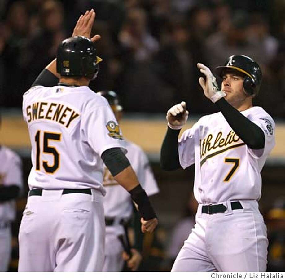 Athletics' center Bobby Crosby does a three run home run during the eighth inning as Oakland Athletics vs.. Kansas City Royals at McAfee coliseum in Oakland, Calif. on Friday, April 18, 2008. He high fives Ryan Sweeney.  Photo by Liz Hafalia / San Francisco Chronicle Photo: Liz Hafalia