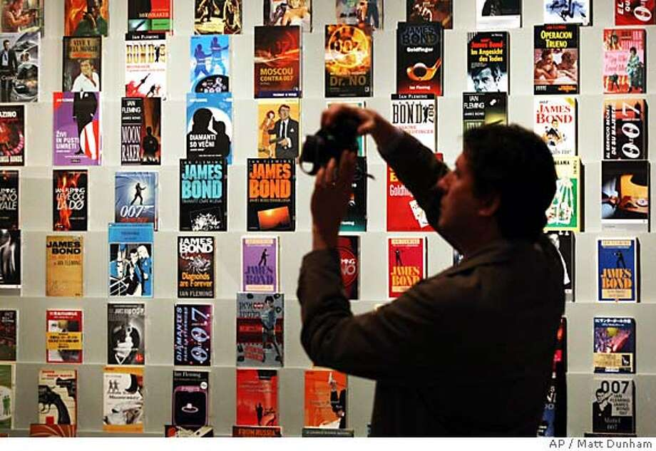 "A man takes photographs beside a display of James Bond books on display at the ""For Your Eyes Only, Ian Fleming and James Bond"" exhibition at the Imperial War Museum in London, Wednesday April 16, 2008. The exhibition, which opens on Thursday, is to celebrate the centenary of Ian Fleming's birth and is the first major exhibition devoted to the life and work of the man who created the world's most famous secret agent, James Bond. (AP Photo/Matt Dunham) Photo: MATT DUNHAM"